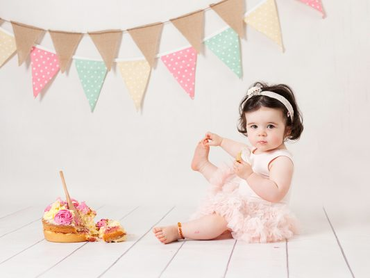 baby girl eating cake on the floor