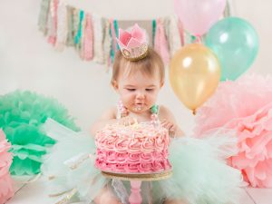 baby girl in a tutu looking at cake smash dublin photography