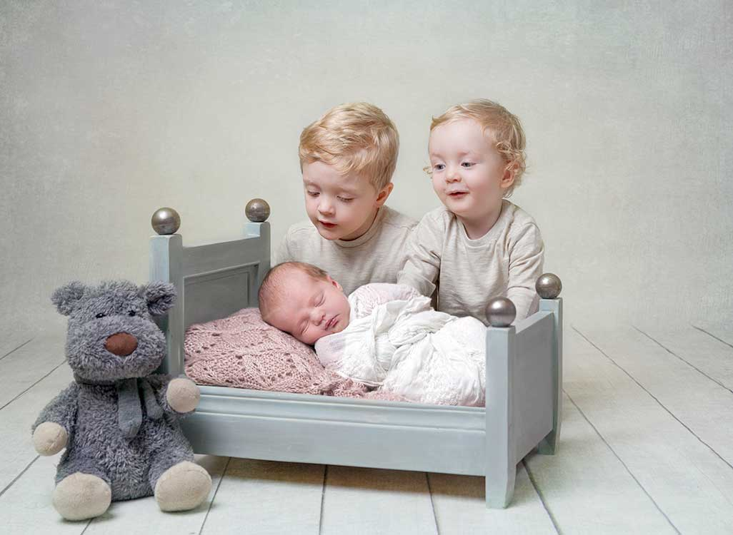 baby in the bed with her brothers looking over